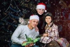 Familia feliz que presenta sobre fondo de la Navidad Feliz Navidad Foto de archivo libre de regalías