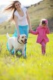 Familia feliz que recorre con el perro Fotos de archivo
