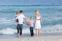 Familia feliz que recorre en la arena Imagen de archivo libre de regalías