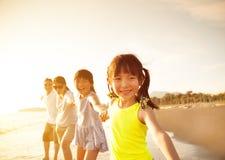 Familia feliz que recorre en la playa Imagen de archivo