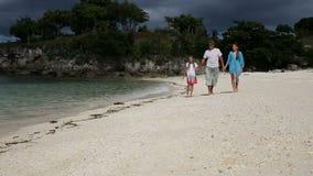 Familia feliz que recorre en la playa almacen de video