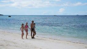 Familia feliz que recorre en la playa metrajes