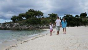 Familia feliz que recorre en la playa almacen de metraje de vídeo