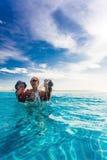 Familia feliz que salpica en piscina azul de un resor tropical Imagen de archivo