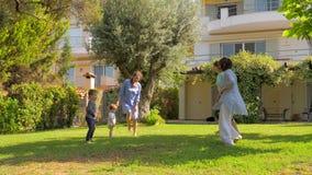 Familia feliz que salta en la cámara lenta en jardín de la casa de lujo, chalet Concepto de las vacaciones de verano Vacaciones d almacen de video