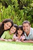 Familia feliz que se acuesta en el jardín Foto de archivo