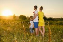 Familia feliz que se coloca al aire libre en el abarcamiento del campo Fotos de archivo libres de regalías