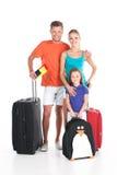 Familia feliz que se coloca con equipaje en el fondo blanco Imagen de archivo libre de regalías