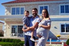 Familia feliz que se coloca delante de nueva casa moderna imagen de archivo libre de regalías