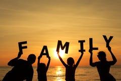Familia feliz que se coloca en la playa en el tiempo de la puesta del sol Imagen de archivo libre de regalías