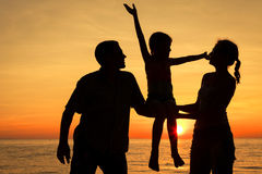 Familia feliz que se coloca en la playa en el tiempo de la puesta del sol Foto de archivo libre de regalías