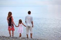 Familia feliz que se coloca en la playa por la tarde Imagen de archivo libre de regalías