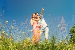 Familia feliz que se coloca en prado en verano Imagen de archivo