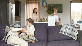 Familia feliz que se divierte con los niños en sala de estar acogedora metrajes