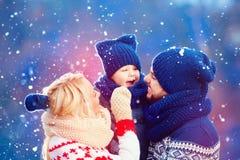 Familia feliz que se divierte debajo de nieve del invierno, vacaciones Foto de archivo