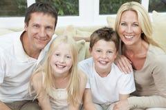 Familia feliz que se divierte el sentarse en el país Foto de archivo libre de regalías
