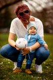 Familia feliz que se divierte en el parque Madre y sus pequeños juegos del hijo Fotografía de archivo