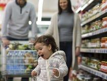 Familia feliz que se divierte en el supermercado imagenes de archivo