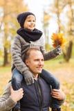 Familia feliz que se divierte en parque del otoño Foto de archivo libre de regalías