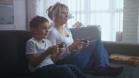 Familia feliz que se divierte que juega la consola del videojuego almacen de video