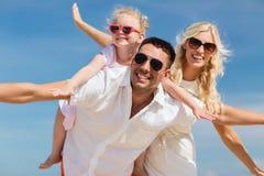 Familia feliz que se divierte sobre fondo del cielo azul Imagenes de archivo