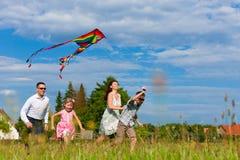 Familia feliz que se ejecuta en prado con una cometa Imagenes de archivo