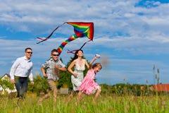 Familia feliz que se ejecuta en prado con una cometa Imagen de archivo