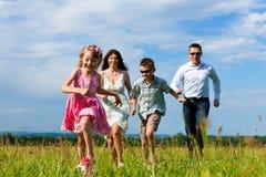 Familia feliz que se ejecuta en prado en verano imágenes de archivo libres de regalías