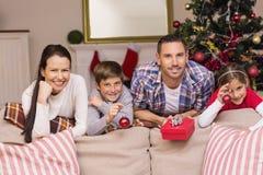 Familia feliz que se inclina en el sofá Imágenes de archivo libres de regalías