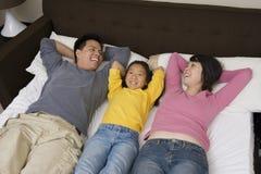 Familia feliz que se relaja en cama Fotos de archivo