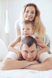 Familia feliz que se relaja en cama Imagen de archivo