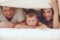 Familia feliz que se relaja en cama Foto de archivo libre de regalías
