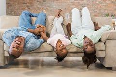 Familia feliz que se relaja en el sofá foto de archivo