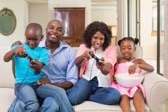 Familia feliz que se relaja en el sofá que juega a los videojuegos Fotografía de archivo libre de regalías