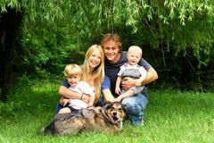 Familia feliz que se sienta debajo de Willow Tree Imagenes de archivo