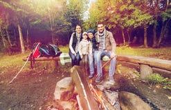Familia feliz que se sienta en banco en el fuego del campo Imagen de archivo libre de regalías