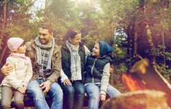 Familia feliz que se sienta en banco en el fuego del campo Fotos de archivo