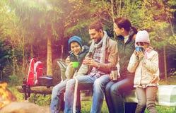 Familia feliz que se sienta en banco en el fuego del campo Fotografía de archivo libre de regalías