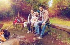 Familia feliz que se sienta en banco en el fuego del campo Imagen de archivo