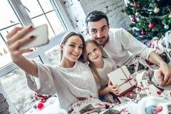 Familia feliz que se sienta en cama y que toma la imagen del selfie con smartphone en casa fotografía de archivo