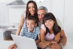 Familia feliz que se sienta en cocina usando su ordenador portátil Imagenes de archivo