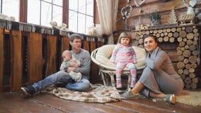 Familia feliz que se sienta en el piso cerca de la chimenea almacen de video