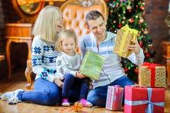 Familia feliz que se sienta en el piso cerca del árbol de navidad imagenes de archivo