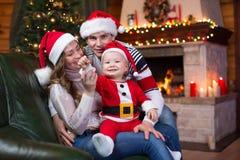 Familia feliz que se sienta en el sofá cerca del árbol de navidad y de la chimenea en sala de estar Imagen de archivo