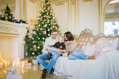 Familia feliz que se sienta en el sofá con un conejo Foto de archivo