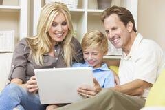 Familia feliz que se sienta en el sofá usando el ordenador portátil Fotografía de archivo