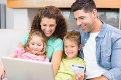 Familia feliz que se sienta en el sofá usando el ordenador portátil junto para hacer compras en línea Imágenes de archivo libres de regalías