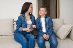Familia feliz que se sienta en el sofá y que usa la tableta digital en casa foto de archivo