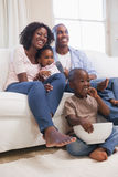 Familia feliz que se sienta en el sofá junto que ve la TV Fotografía de archivo libre de regalías