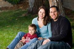Familia feliz que se sienta en hierba Imagen de archivo